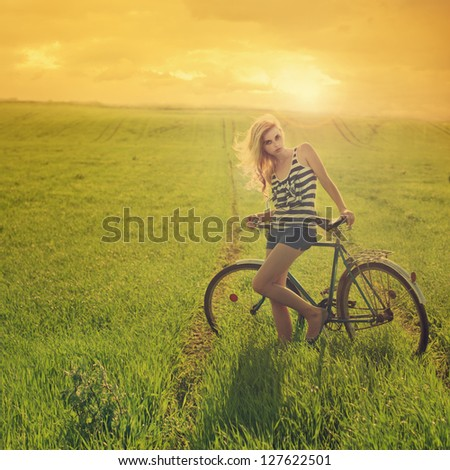 beautiful young woman with an old bicycle at sunset in the field - stock photo