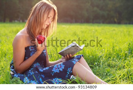 Beautiful young woman with apple in hands sitting in the grass and reading a book on a background of green nature