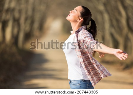 beautiful young woman with arms outstretched outdoors - stock photo