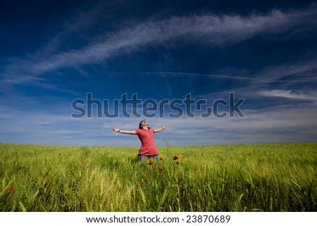 beautiful young woman with arms wide open happy in the nature - stock photo