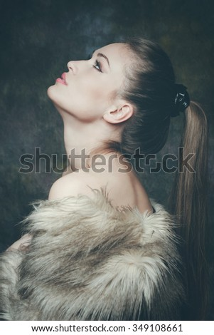 beautiful young woman with artificial fur  portrait, studio shot, profile