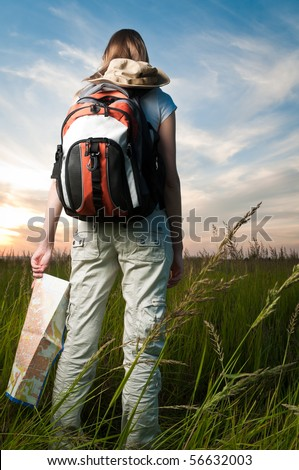 beautiful young woman with backpack and map in hand standing outside in the field with her back to camera. Sunset cloudy blue sky in background and green grass in foreground - stock photo