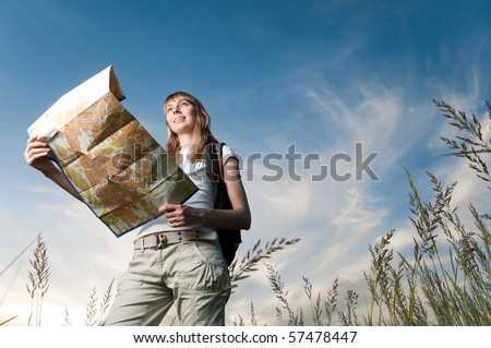 beautiful young woman with backpack and map in hands standing outside in the field and looking in front of her. Blue cloudy sky in background and green grass in foreground - stock photo