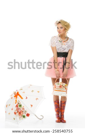 Beautiful young woman with basket of flowers and umbrella standing nearby - stock photo