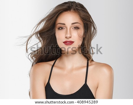 Beautiful young woman with beauty long curly hair. Fashion model posing at studio. - stock photo