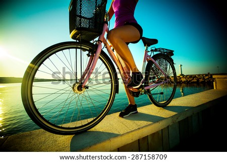 Beautiful young woman with bicycle on sunrise near a sea. Activity. - stock photo