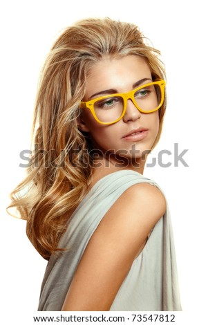 beautiful young woman with big blond long hair wearing yellow acetate frame glasses on white background. - stock photo
