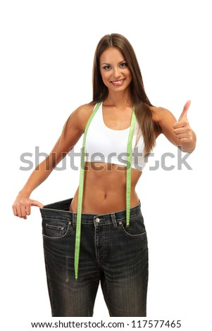 beautiful young woman with big jeans and measuring tape, isolated on white - stock photo