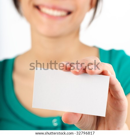 Beautiful young woman with big smile displaying blank business card. Shallow depth of field, focus on card. Isolated on white. - stock photo