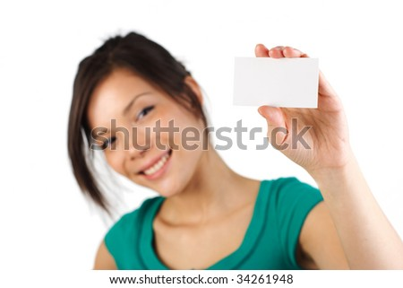 Beautiful young woman with big smile displaying blank business card. Shallow depth of field, focus on card. Isolated on white background. - stock photo