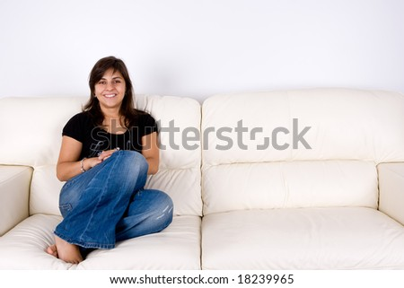 beautiful young woman with black shirt sitting in white sofa - stock photo