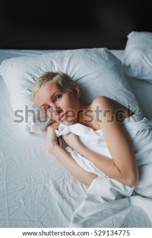 Beautiful young woman with blond short hair lying on the bed on white linen. Gentle innocent look. Impression of morning awakening