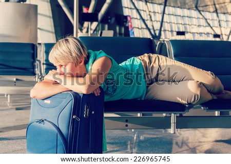 beautiful young woman with blond short hair with a suitcase at the airport and waiting for her flight - stock photo