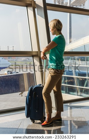 beautiful young woman with blond short hair with a suitcase at the airport and waiting for her flight