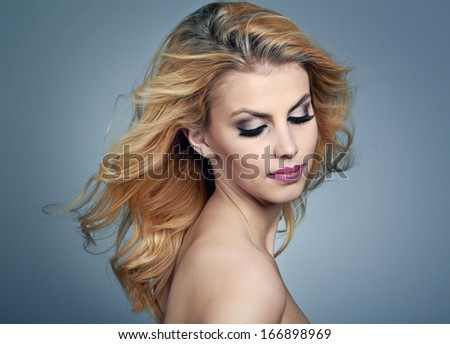 Beautiful young woman with blonde hair and evening make up