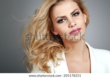 Beautiful young woman with blonde hair. Pretty model poses at studio.