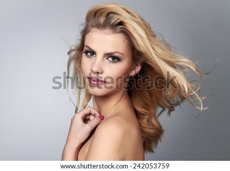 Beautiful young woman with blonde hair. Pretty model poses at studio.  - stock photo