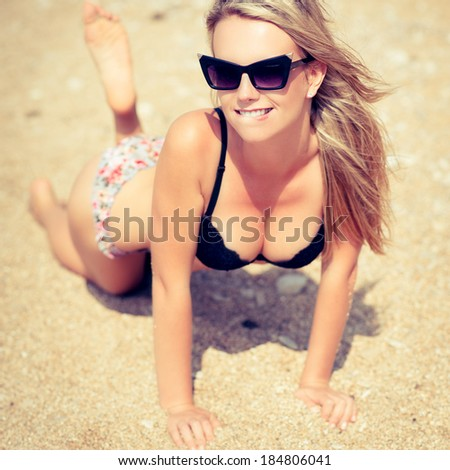 beautiful young woman with blowing hair relaxing on sand at a beach. Photo toned style instagram filters - stock photo