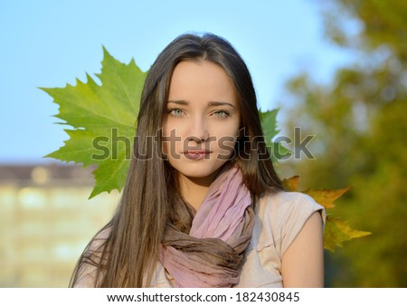 Beautiful young woman with blue eyes and blond hair posing outside in autumn - stock photo