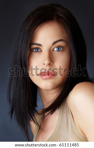 beautiful young woman with blue eyes and dark hair in structured bob haircut. - stock photo