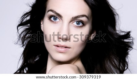 beautiful young woman with blue eyes, flawless skin and perfect make-up - stock photo