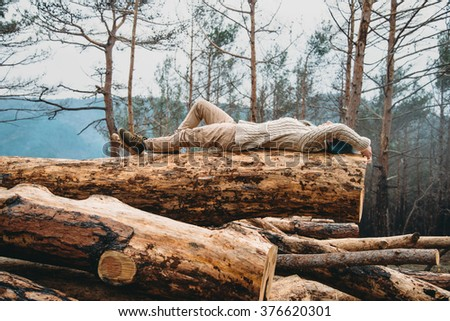 Beautiful young woman with blue hair lying on fallen tree trunk. Girl resting outdoor - stock photo