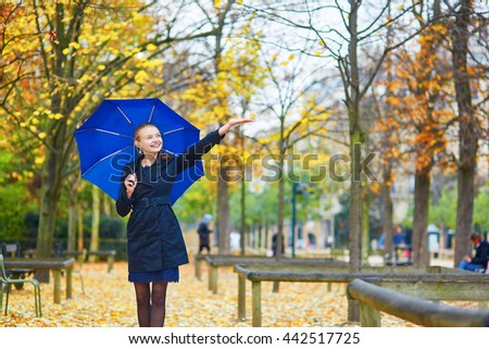 Beautiful young woman with blue umbrella in the Luxembourg garden of Paris on a fall or spring rainy day