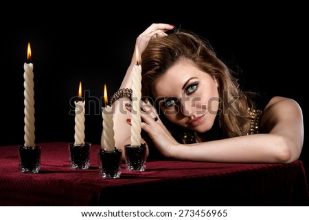 Beautiful young woman with bright green eyes near the candles over black background - stock photo