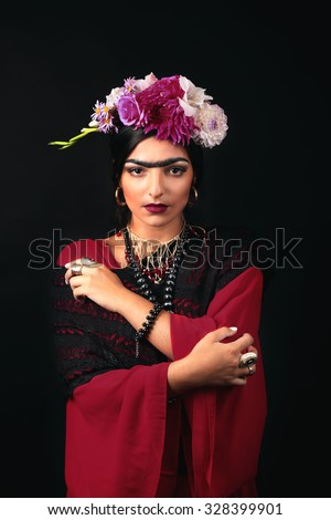 Beautiful young woman with bright make up and flowers in hair looking like Frida Kahlo. Over black background - stock photo