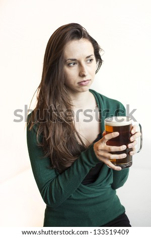 Beautiful young woman with brown hair and eyes holding a mug of beer.