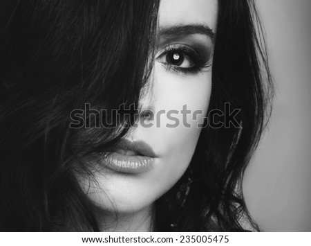 beautiful young woman with brown hair and perfect skin posing on grey background - stock photo
