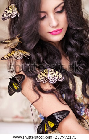 Beautiful young woman with butterfly. Spring mood. - stock photo