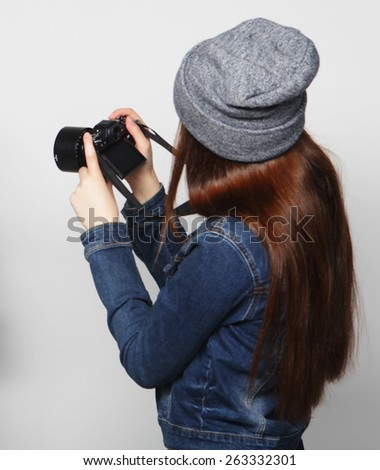Beautiful young woman with camera over gray background - stock photo