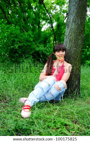 Beautiful young woman with candy outdoor. - stock photo
