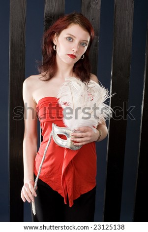 Beautiful young woman with carnival mask - stock photo