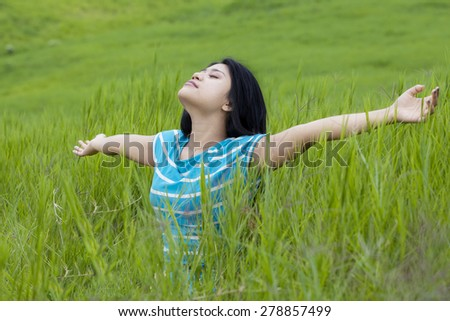 Beautiful young woman with casual clothes enjoying freedom while breathe fresh air and outstretched hands on the meadow - stock photo