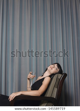 Beautiful young woman with champagne sitting on chair in front of curtains - stock photo