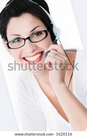 Beautiful young woman with charming big green eyes is bearing modern glasses and receiving calls on a headset. - stock photo