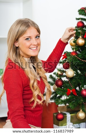 Beautiful young woman with Christmas tree,Decorating Christmas tree - stock photo