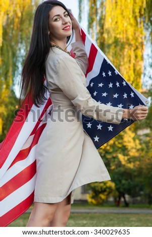 Beautiful young woman with classic dress holding american flag in the park. fashion model holding us smiling and looking at camera. business style clothing usa lifestyle.