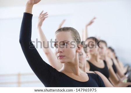 Beautiful young woman with classmates practicing at the barre in ballet rehearsal room - stock photo