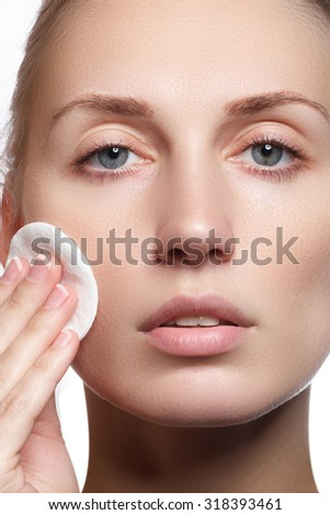 Beautiful young woman with clean fresh skin close-up. Beautiful woman face close up studio on white. Beautiful young woman touching her face. Fresh healthy skin. Isolated on white - stock photo