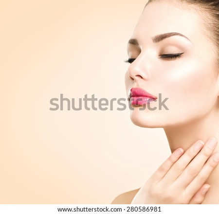 Beautiful Young Woman with Clean Fresh Skin close up over beige background. Beauty Portrait. Spa Woman Smiling, touching her skin. Perfect Fresh Skin. Pure Beauty Model. Youth and Skin Care Concept  - stock photo