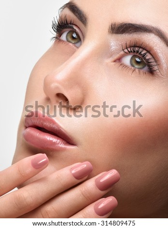 Beautiful Young Woman with Clean Fresh Skin. Close up Portrait.  Fashion Model Girl Face. Perfect Skin. Professional Makeup. Fashion shiny highlighter on skin, sexy gloss lips. Perfect manicure. - stock photo