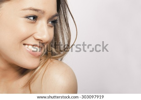 Beautiful young woman with clean fresh skin. Close up portrait, studio shot. Horizontal. - stock photo