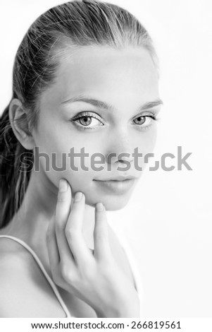 Beautiful young woman with clean fresh skin on light background