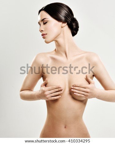 Beautiful young woman with clean skin nude topless breasts. Beautiful woman covering her nude breast. - stock photo