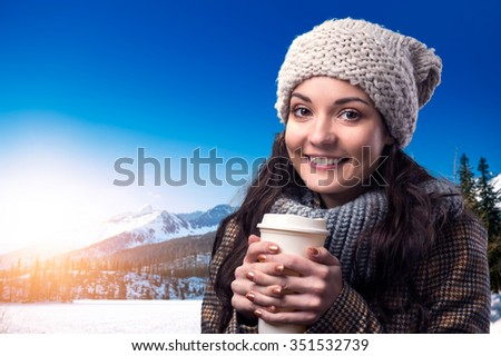 Beautiful young woman with coffe cup enjoying a walk in mountains