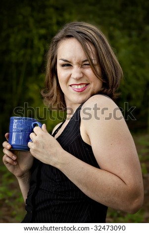 Beautiful Young Woman with coffee cup outdoors smiling and winking.