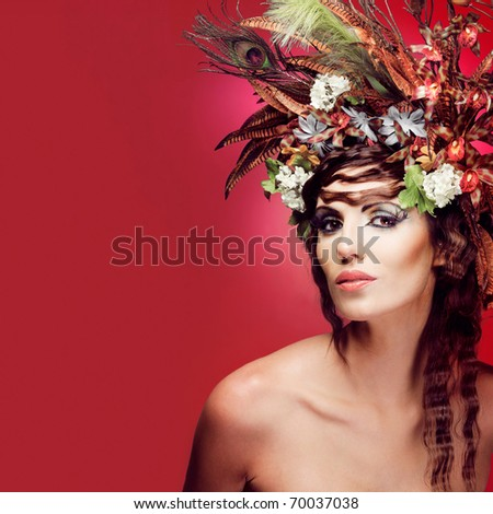 Beautiful young woman with colorful flowers in hair.